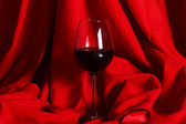 Glass of red wine on red cloth