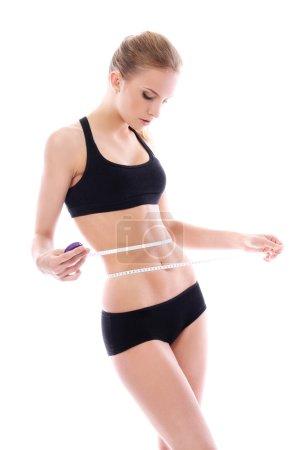 Beautiful woman measuring her waistline