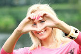 Happy blonde forming heart with her hands