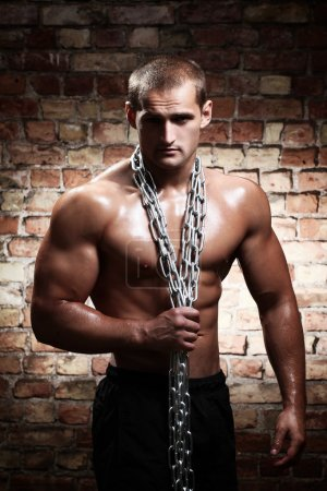 Muscular guy with chains on his shoulders