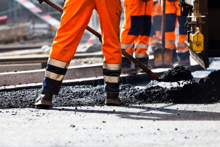 Photo for Workers on a road construction, industry and teamwork - Royalty Free Image