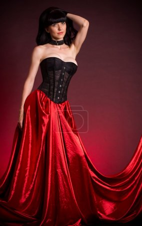 Sexy young woman in fashion dress on red background.