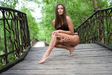 Sexy young girl on a pedestrian bridge