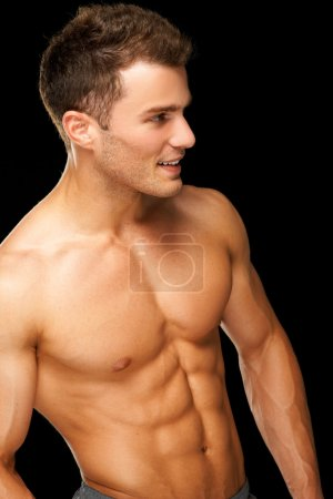 Portrait of a male athlete muscular on black