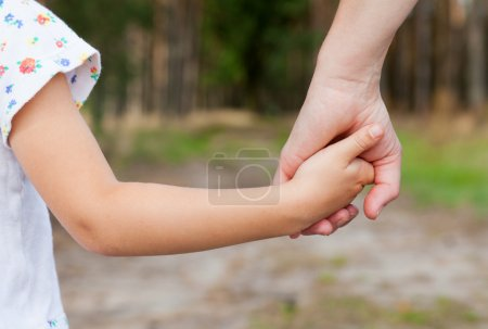 Photo for Mother holding a hand of her doughter in spring day outdoors - Royalty Free Image