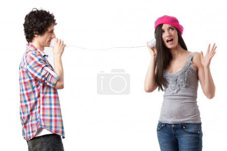 Photo for Lovely couple talking on a tin phone isolated on white. - Royalty Free Image