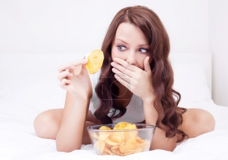 Photo for Pretty woman eating potato chips in bed at home and scared of gaining weight - Royalty Free Image