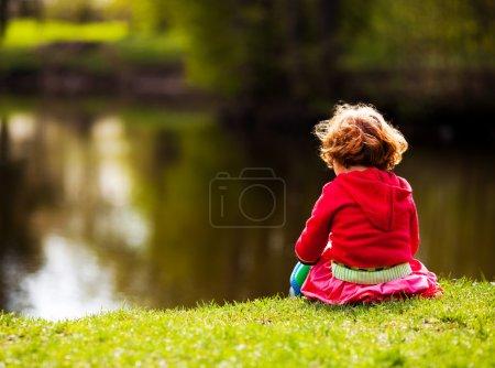 Photo pour Fille de cinq ans assis sur le bord de la rivière sur une journée d'été - image libre de droit