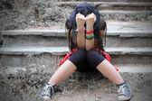 Ragazza adolescente con volto nascosto nelle sue mani