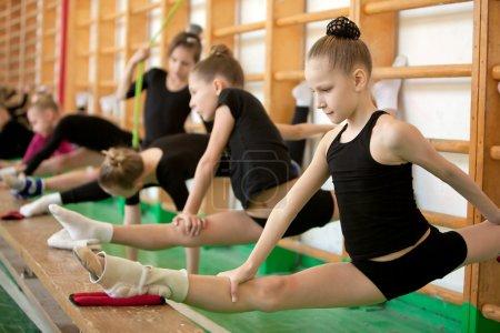 Photo pour Former les jeunes gymnastes dans la salle, étirement - image libre de droit