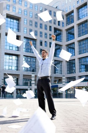 Photo for Young businessman standing front his building office and throwing away his papers, Never felt so good - Royalty Free Image