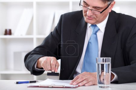 Photo pour Homme d'affaires senior se concentrer sur le document d'estampillage, approuver le contrat - image libre de droit