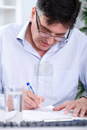 Photo for Senior concentrated business man writing in office - Royalty Free Image