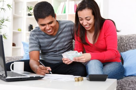 Smiling couple paying bills at home