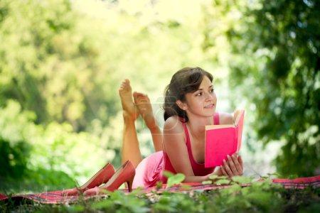 Photo pour Belle femme avec un visage heureux et la lecture dans la nature - image libre de droit