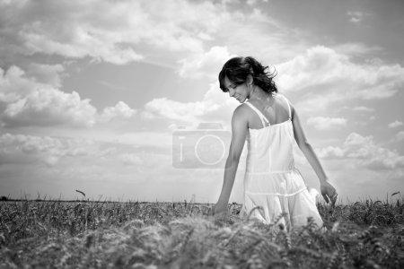 Photo pour Jeune femme marchant à travers le champ de blé touchant le blé, noir et blanc - image libre de droit