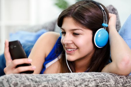 Teenager holds smartphone and listens to music