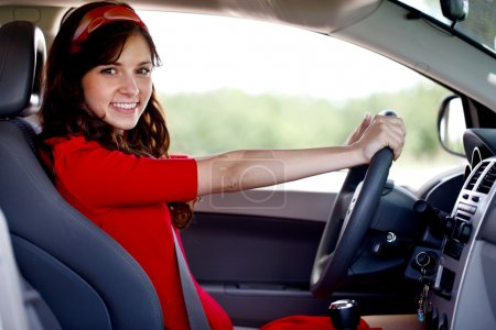 Happy smiling woman driving car