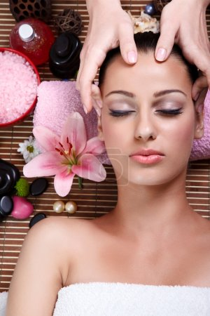 Photo for Close up portrait of a young woman with eyes closed receiving facial massage - Royalty Free Image
