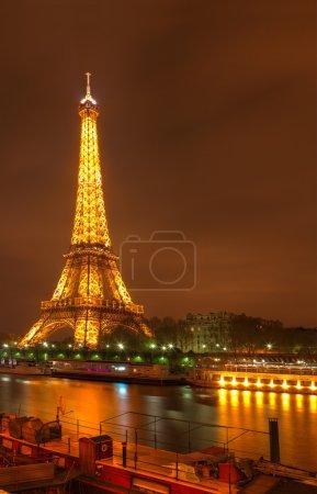 Photo pour Paris, france, 31 mars 2012 : image de la nuit à paris de la tour eifel illuminée, la seine et une partie d'une tour ship.the spécifique s'élève à 324 mètres de haut et est le plus important symbole de paris et en france. - image libre de droit