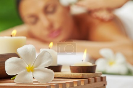 Photo for Portrait of young beautiful woman in spa environment. blurred face, focused on flower. - Royalty Free Image