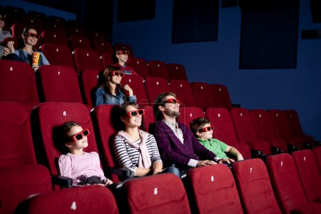 Parents with children watching a comedy