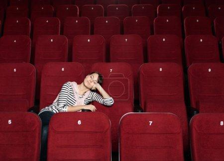 Photo pour Femme la sieste après le film au cinéma - image libre de droit