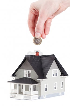 Photo for Real estate concept - hand putting coin into house architectural model, isolated - Royalty Free Image