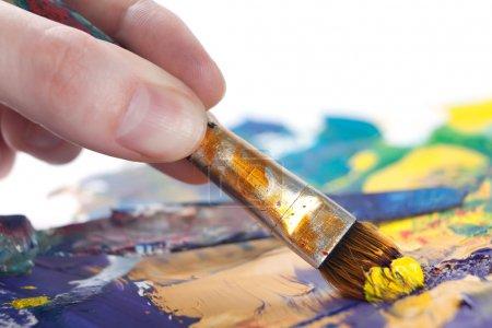 Photo pour Quelqu'un peint un tableau avec un pinceau, isolé sur fond blanc - image libre de droit
