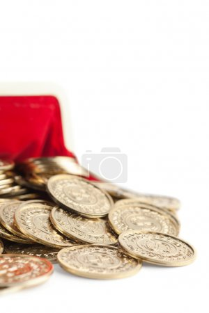 Scattered gold coins are in hot red purse, isolated on white