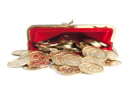 Scattered gold coins are in hot red purse, isolated on white background