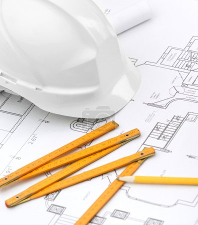 Photo for White hard hat near working stuff: drawings, pencil, rule for building needs - Royalty Free Image