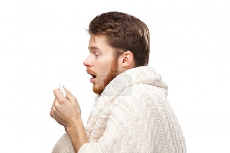 Sneezing young man holding wipes