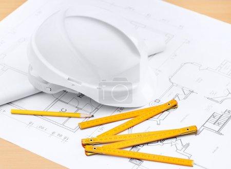Photo pour Chapeau dur blanc près des dessins de travail, crayon, règle pour les besoins de construction - image libre de droit