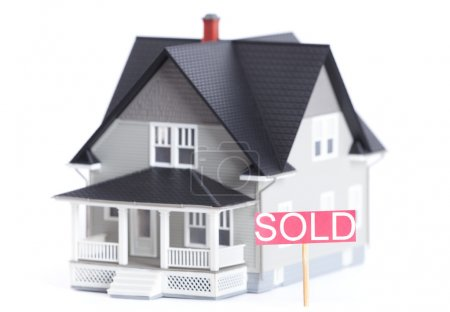 Household architectural model with Sold sign, isolated