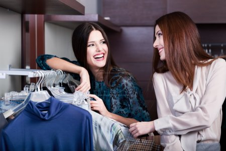 Friends do shopping at the store with great choice of clothes
