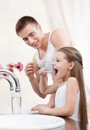 Photo pour Père enseignants sa fille pour nettoyer les dents dans la salle de bain - image libre de droit