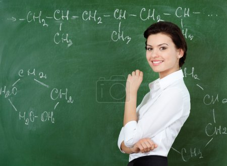 Smiley teacher hands chalk standing at the blackboard