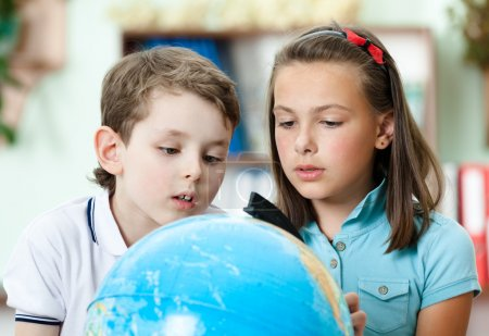 Two friends examine a school globe