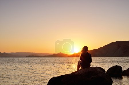 Photo for Girl on the beach watching the sunset - Royalty Free Image