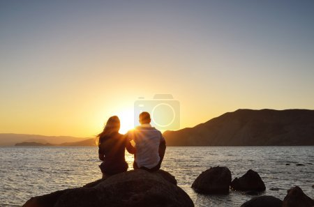 Photo for Young couple sitting on a rock near the sea and watching the sun - Royalty Free Image