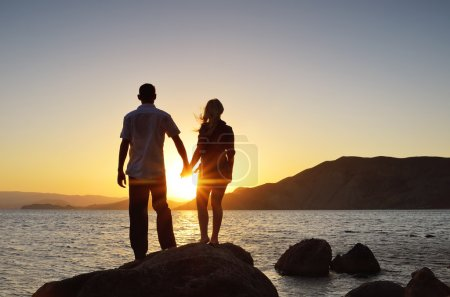 Photo for Girl and boy holding hands and watching the sun by the sea - Royalty Free Image