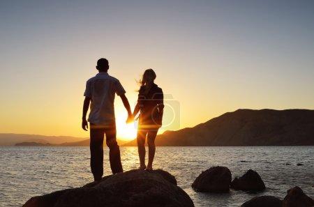 Photo pour Fille et garçon tenant la main et regardant le soleil par la mer - image libre de droit