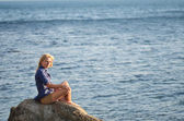 Girl is sitting on a rock near the sea