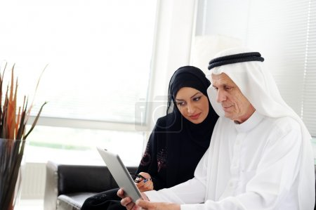 Two couple muslim lookig at tablet on office