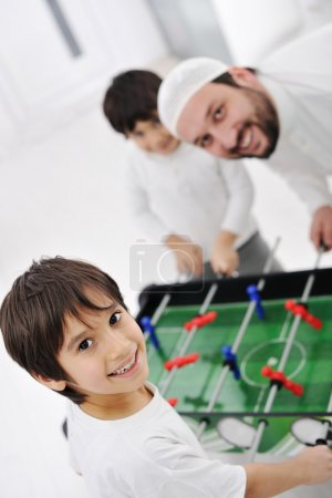 Arabic family playing at home together, father and kids