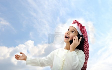 Arabic kid talking on phone outside