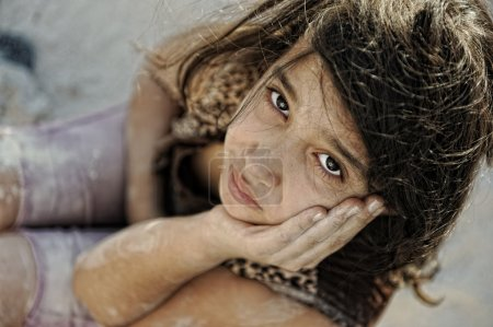 Poverty and poorness on the children face. Sad little girl. Refugee. War results.