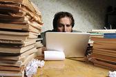 Podnikatel v office na notebook. chaotický stůl s mnoha knih o