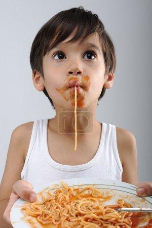 Photo for Kid eating spaghetti - Royalty Free Image